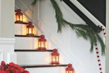 mini red candle lanterns on each step, poinsettia arrangements, a fir garland and candy canes on the railing for Christmas