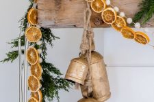 natural Christmas mantel decor with a fir garland, dried citrus, pompoms and large vintage bells is very chic and beautiful