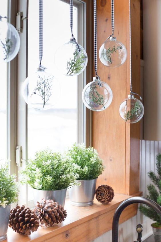 natural Christmas window decor with potted greenery, large pinecones, sheer ornaments with greenery inside is beautiful