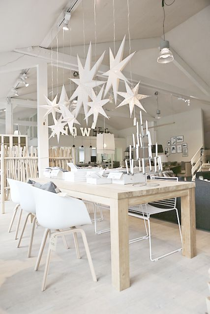 oversized white lasercut stars hanging over the table and an advent candelabra for a real Nordic feel in the space