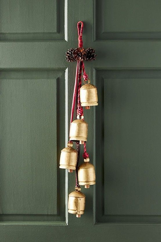 pinecones and vintage bells cna be hung on your front door instead of a usual Christmas wreath and they will bring a rustic holiday feel