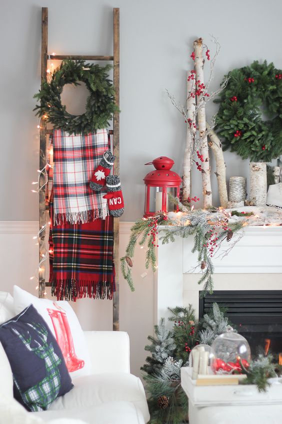 plaid scarves, mittens and a fir wreath and lights on the ladder, branches, berries and a red lantern on the mantel feel very rustic