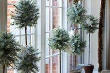 potted mini trees and a branch with lots of birds for creative and very chic Christmas window decor