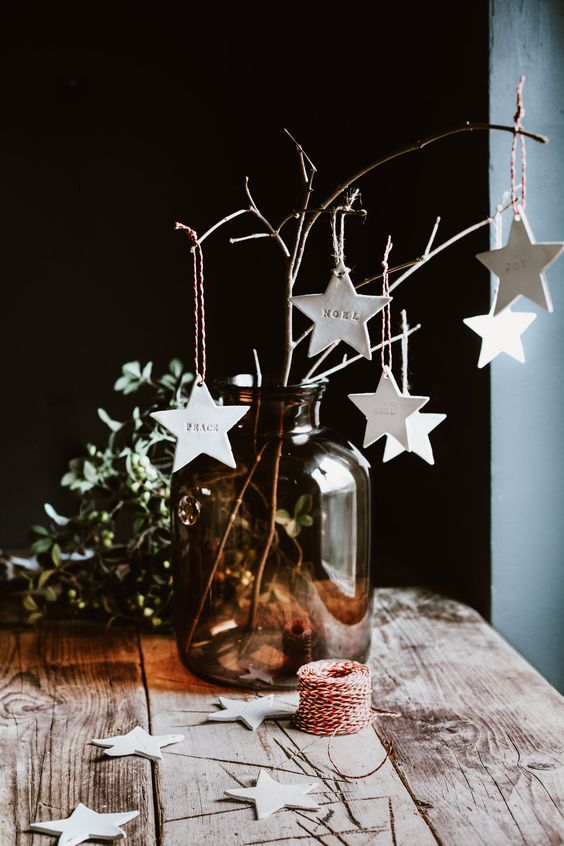 pretty Christmas decor with a large apothecary bottle with branches, white clay star ornaments is a lovely and easy idea