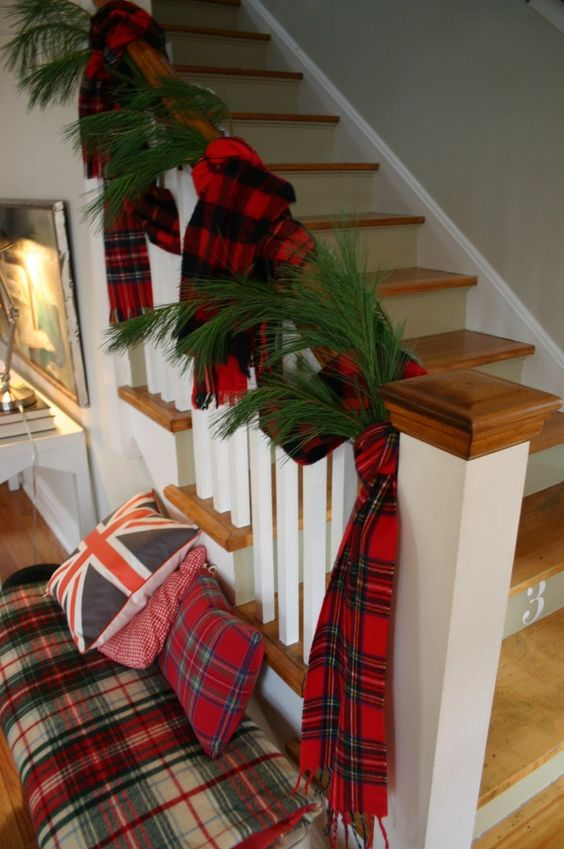 pretty Christmas decor with evergreens and plaid scarves on the railing, a plaid bench with plaid pillows is very cozy