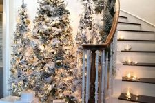 a cluster of christmas trees is a nice way to decorate the space by a staircase
