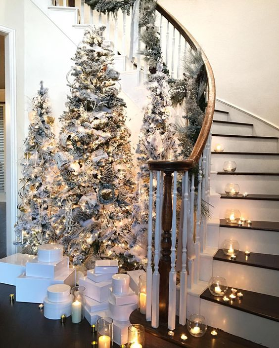 pretty and chic Christmas staircase decor with little tealights and candleholders and a cluster of flocked Christmas trees in the entryway