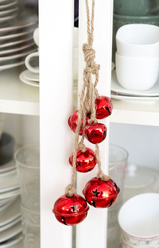 pretty red Christmas bells on rope can be hung on furniture or doors to bring a slight holiday feel to the space