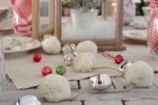 pretty rustic Christmas decor with red, gold and green ornaments and white pompoms plus bells is lovely