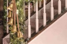 railings decorated with a greenery and fir branch garland, with lights and large vintage bells will make your space feel Christmassy