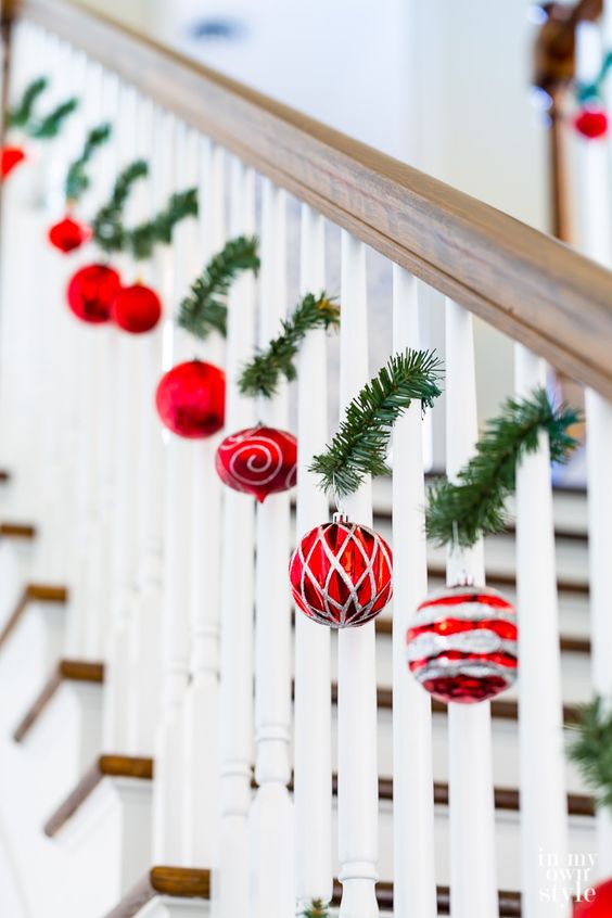 red and silver ornaments hanging on tiny evergreen twigs attached to the railing will delicately and chic decorate the space