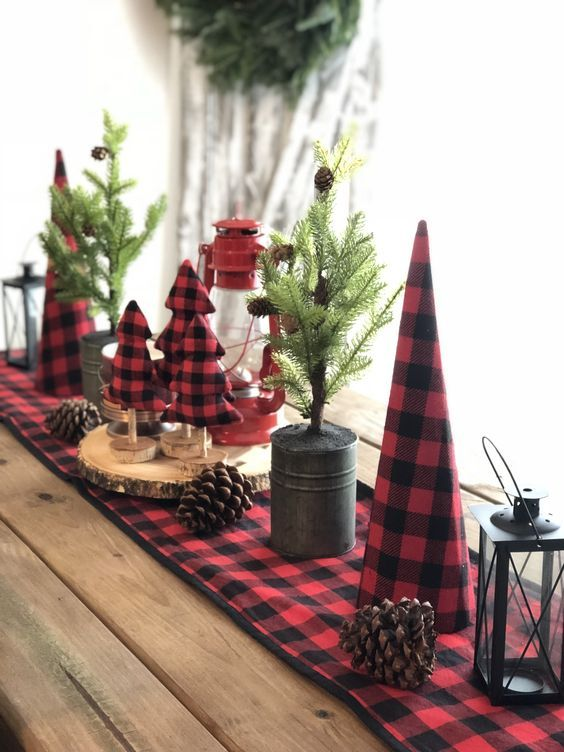 rustic Christmas table decor with a plaid runner and plaid felt trees, pinecones, a red lantern and mini trees in buckets