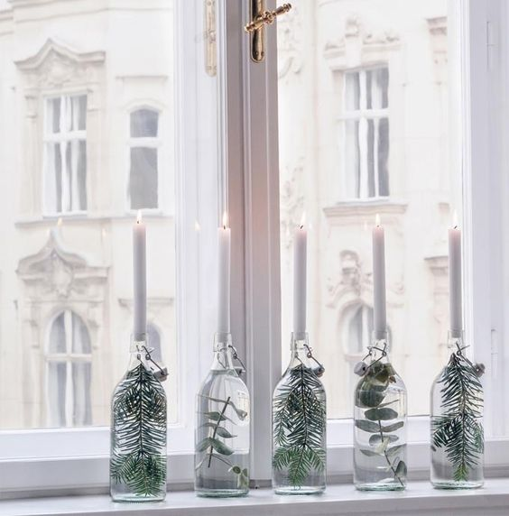 sheer bottles with foliage and greenery and white candles on top are amazing for table or windowsill decor are great