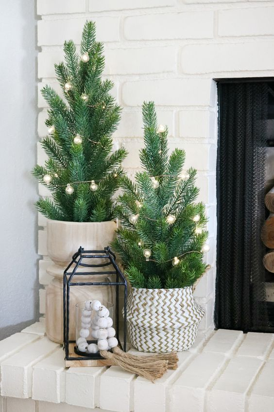 small Christmas trees with lights, in wooden and woven baskets, a lantern with wooden beads is a lovely Nordic decor idea