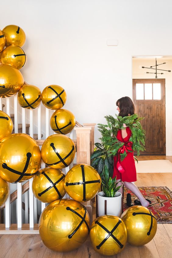 stairs decorated with oversized Christmas bell balloons and fir branches look fun, bold and very festive