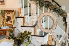vintage Christmas stairs decor with vintage books, candles, wooden letters, fir branches and burlap ribbon feels rustic and cozy