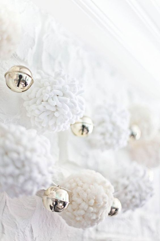 white pompom garlands with bells are very cozy and refined decorations for Christmas