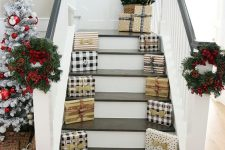 wrapped gift boxes lining up the staircase, bold blooms, wreaths and a mini tree in a basket on the stairs