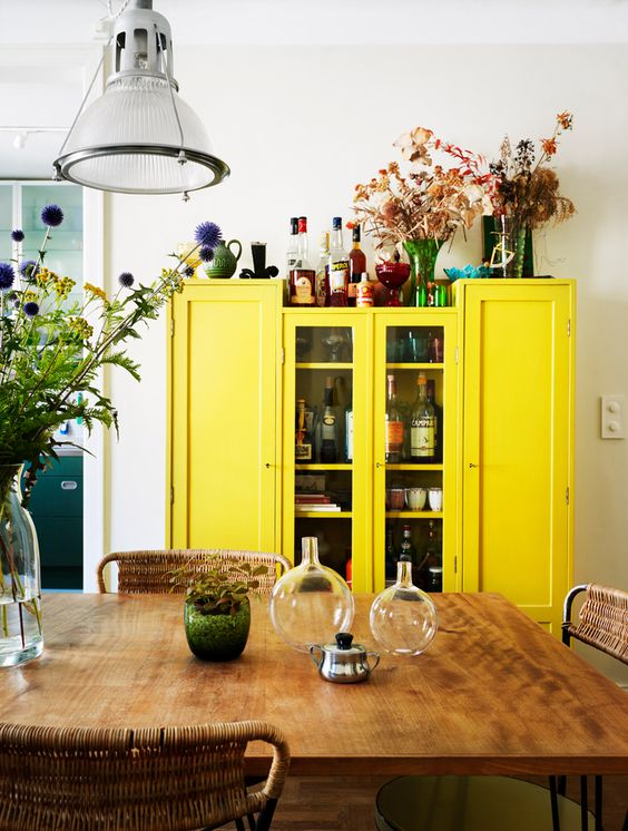 a boho dining room with a wooden table, wicker chairs, a sunny yellow storage units, lots of blooms and pretty vases