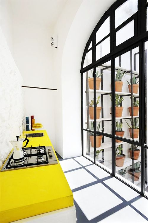 a bold minimalist kitchen in white, with yellow countertops and touches of black looks bold and sunshine-filled