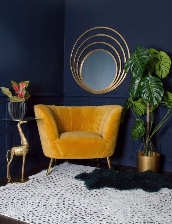 a bright and refined nook with navy walls, layered rugs, a yellow chair, some touches of gold and statement plants