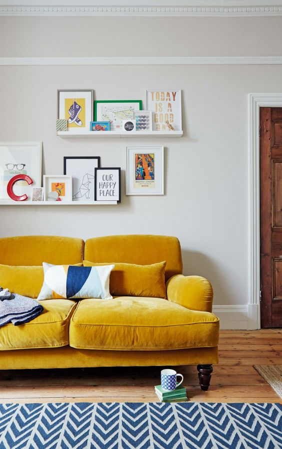 a bright modern living room with a mustard sofa, a navy chevron rug and ledges with books and artworks