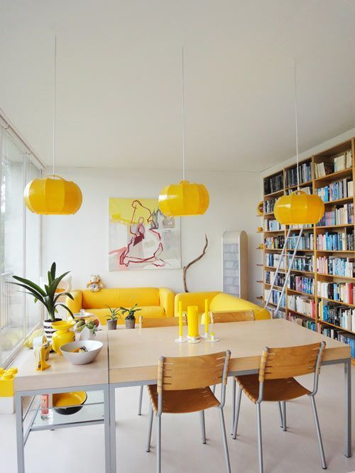 a bright open layout with yellow sofas, candles and paper pendant lamps that enliven the space a lot