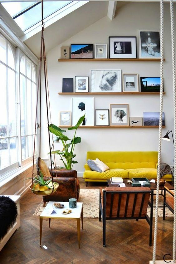 a catchy attic living room accented with a lemon yellow sofa, with ledges with art, leather chairs and potted plants
