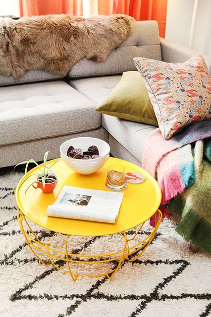 a colorful living room accented with a bright yellow round coffee table and bright linens is a very fun and cool space