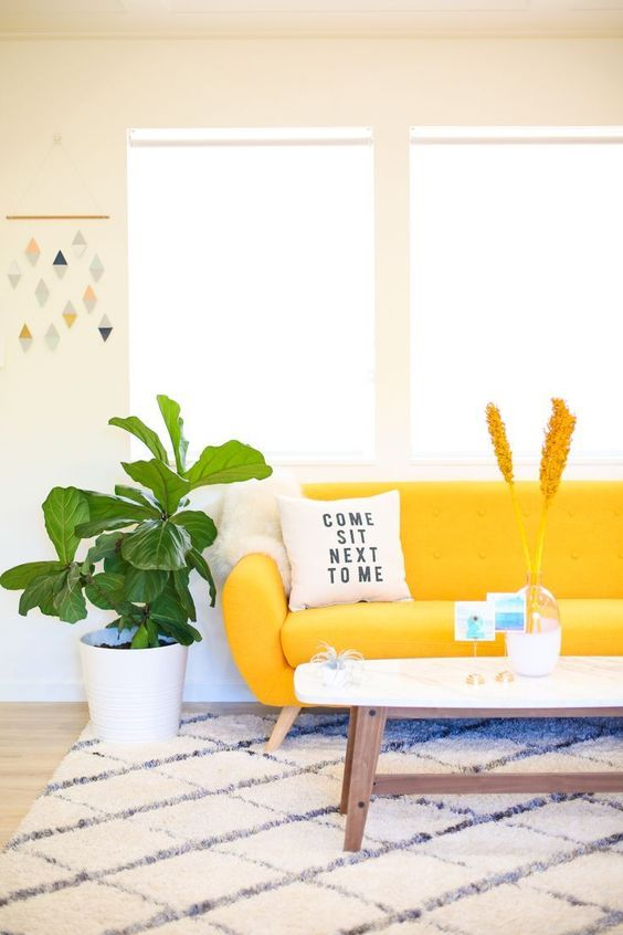 a cozy mid-century modern living room with a bright yellow sofa that add color and makes a statement here