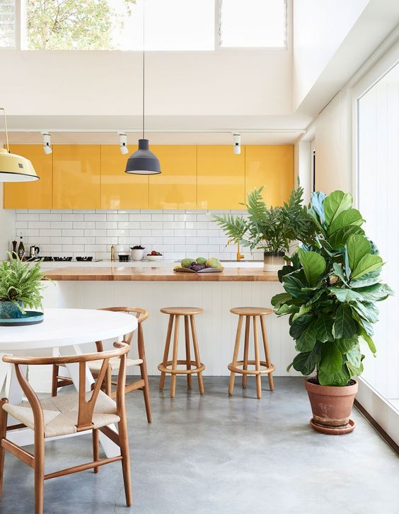a neutral minimalist kitchen accented with yellow upper cabinets that add color to the space and make it bolder and cooler