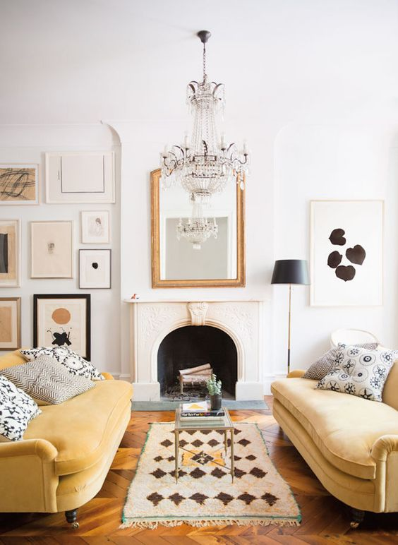 a refined monochromatic living room with a chic gallery wall, a non-working fireplace, a crystal chandelier and yellow sofas