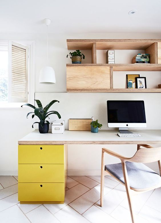 a neutral mid-century modern home office with wood and plywood furniture and bold yellow drawer fronts to spruce the room with color