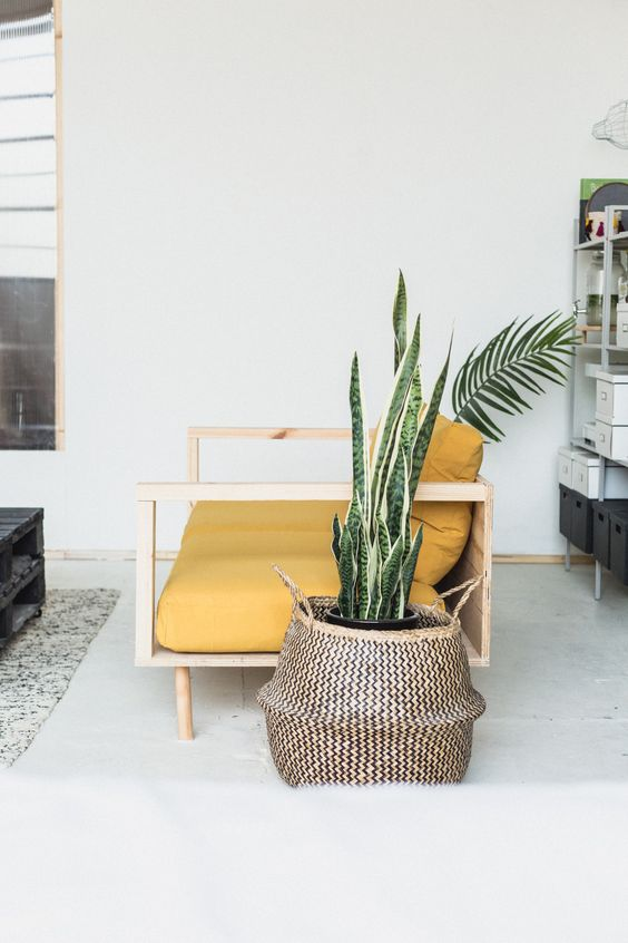 a neutral boho space with a mustard loveseat that immediately makes a statement with its color and simple design