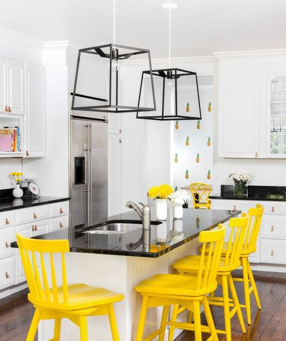 a modern farmhouse kitchen in black and white highlighted with playful pineapple print wallpaper and sunny yellow chairs