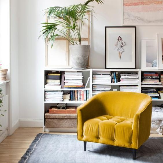 an all-neutral reading nook is made interesting and catchy with a chic mustard yellow chair that is a centerpiece here