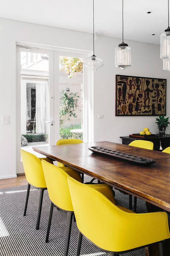 a stylish dining room with a wooden table, a dark cabinet, lemon yellow chairs and pretty pendant lamp plus unique artworks