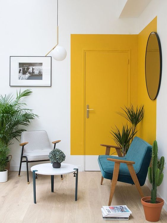 color blocking with mustard paint accents the sitting zone and highlights the door adding a sunny touch to the space
