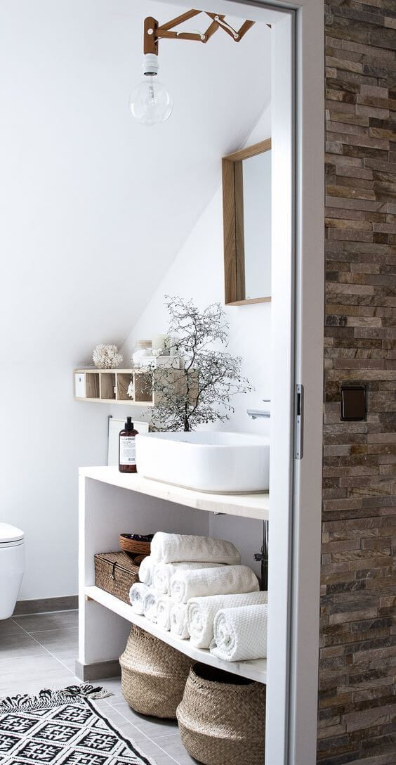 a Nordic bathroom with a vanity and baskets for storage, a wooden shelf and a mirror in a wooden frame