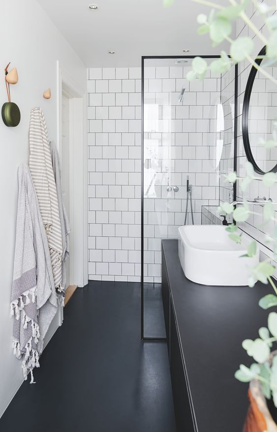 a Nordic bathroom with white square tiles, sleek black surfaces, black framing and a curved sink is very chic