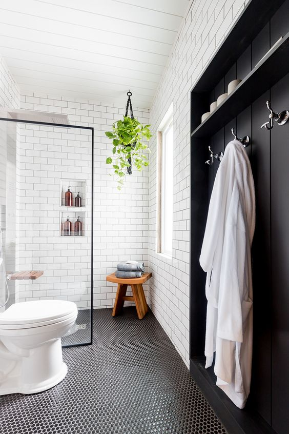 a Nordic bathroom with white subway and black penny tiles, a wooden built-in piece, some greenery and niches in the shower space