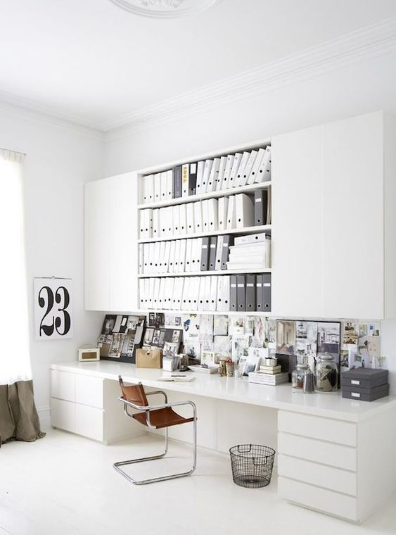 a Nordic home office with a large white desk and an oversized open and closed storage unit over the desk plus a gallery wall in between
