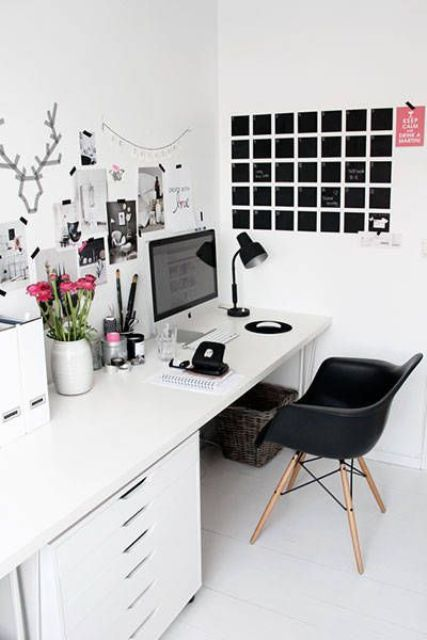 a Nordic home office with a white desk, a black chair, a gallery wall, a memo board and some blooms