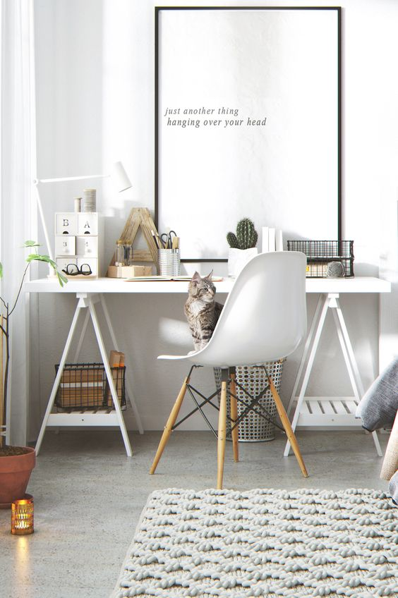 a Nordic home office with a white trestle desk, a white chair, a large artwork, cacti and candleholders is a stylish space