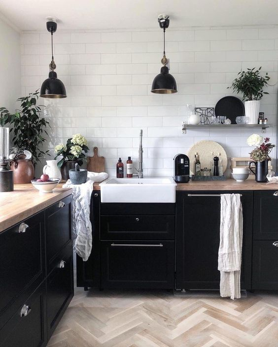 a Nordic kitchen with black cabinetry, butcherblock countertops, black pendant lamps and potted plants to refresh it