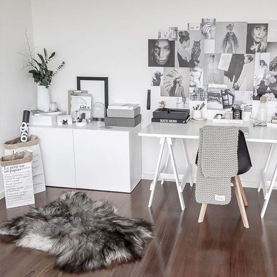 a Noridc home office with a trestle desk, a cabinet, a black chair, a faux fur rug, a gallery wall and some greenery