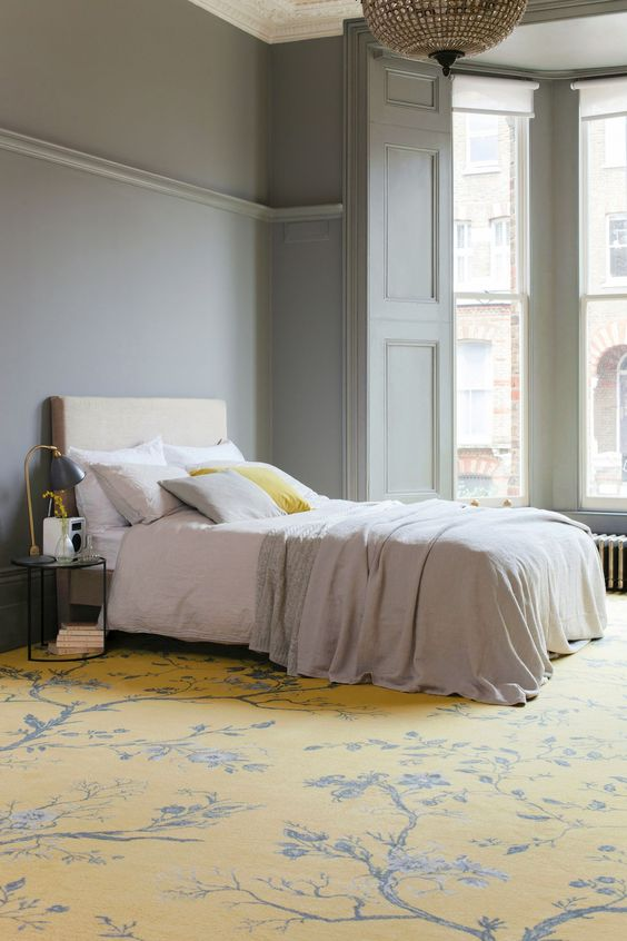 a Parisian style bedroom with grey paneled walls, an upholstered bed, round nightstands, a yellow floral carpet and a crystal chandelier