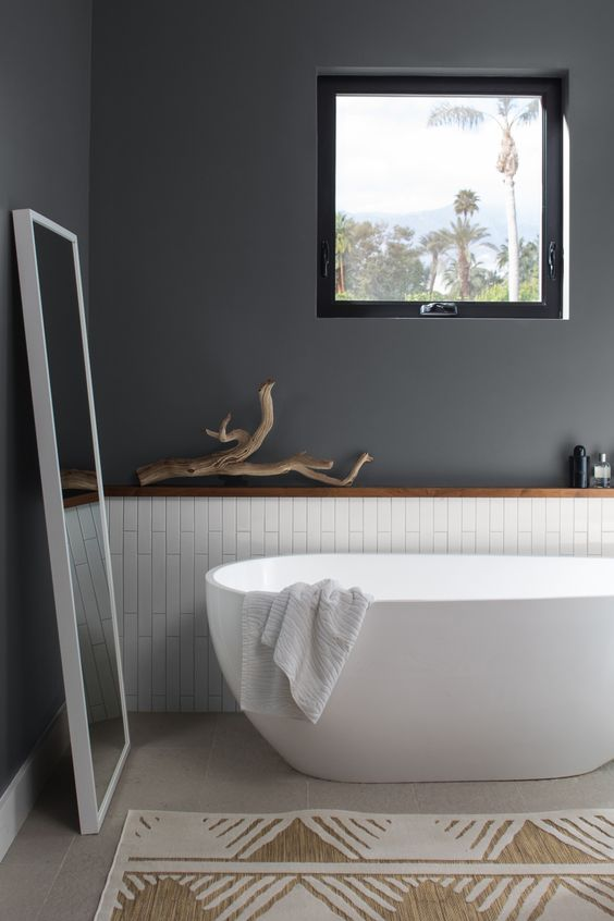 a Scandinavian bathroom with grey walls, white skinny tiles, a free-standing tub, a mirror and a little window