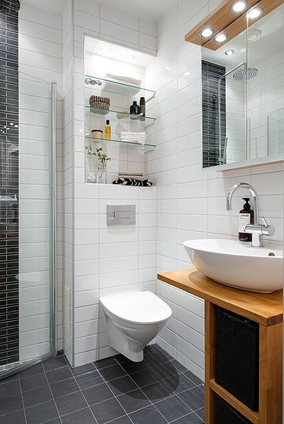 a Scandinavian bathroom with white and grey tiles, with a tiny wooden vanity, a mirror with lights and a niche with shelves
