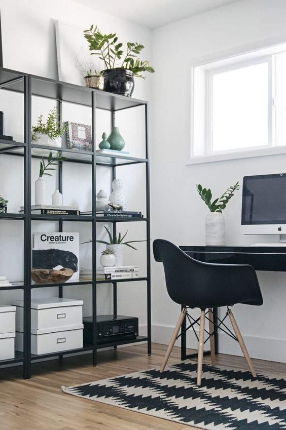 a Scandinavian home office with a black desk and chair, a black open storage unit, a printed rug and some potted plants